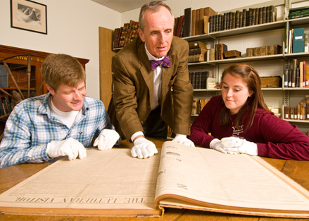 Teacher and two students looking at a book