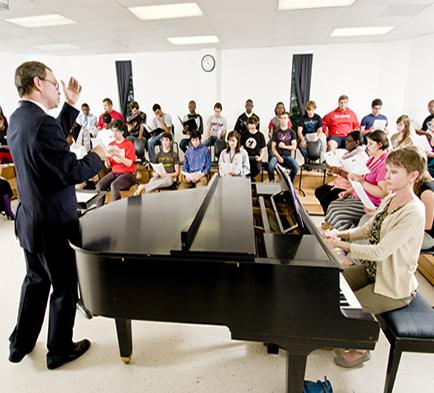 Man directing a chorus class