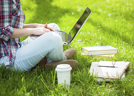Girl sitting on grass using laptop