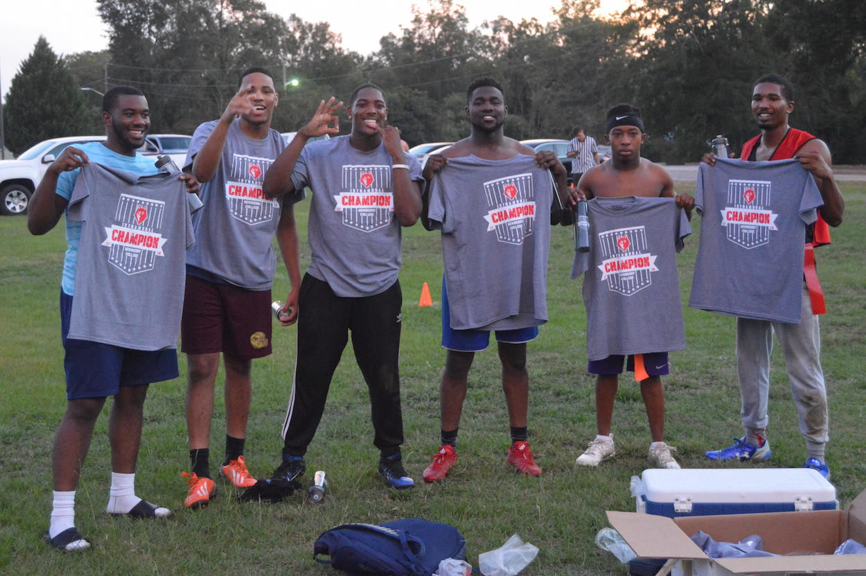 six students showing their intramural champions t-shirts