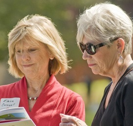 Two alumni looking at a book
