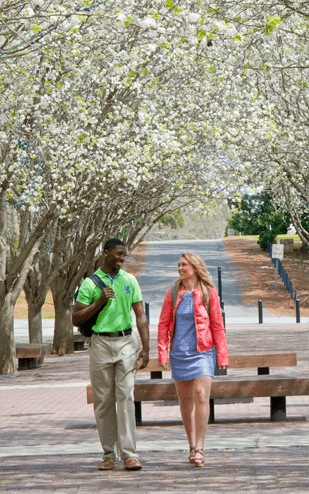 male and female walking through campus in spring